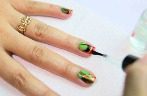 Remove the cello tape and excess nail paint with nail paint remover and apply clear polish on top