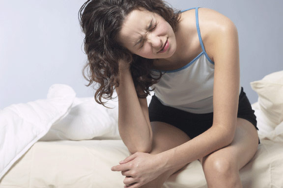 Woman waking up with a headache, see a sleep doctor,