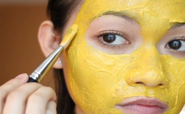 woman applying turmeric face pack, natural remedies to remove sun tan