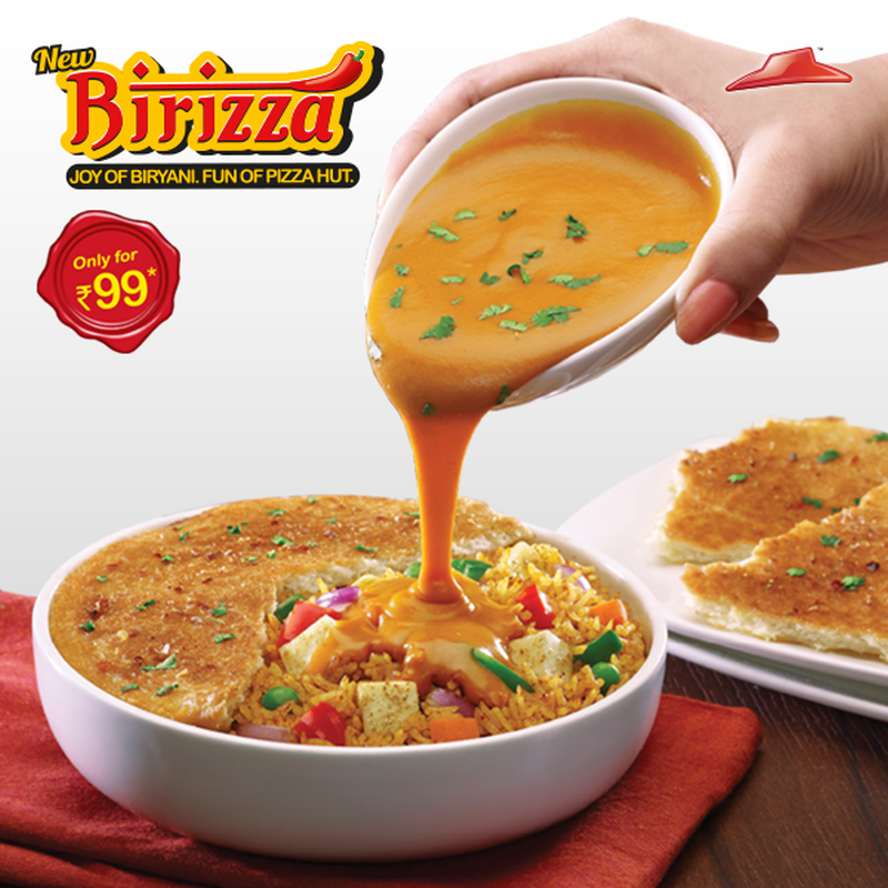 Hand pouring gravy on birizza, Hybrid foods,