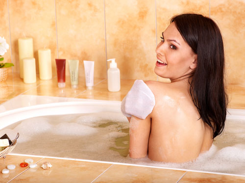 Woman in bath tub looking over her left shoulder, skin and hair