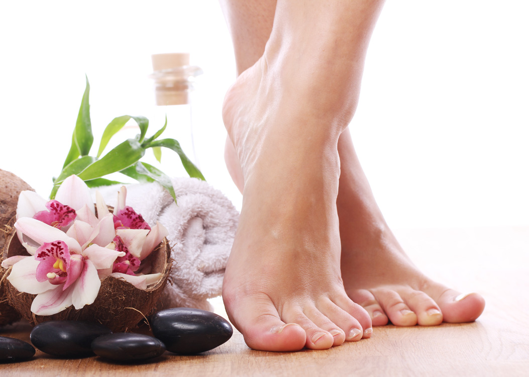 A pair of feet next to flowers, towel and pebbles, skin and hair